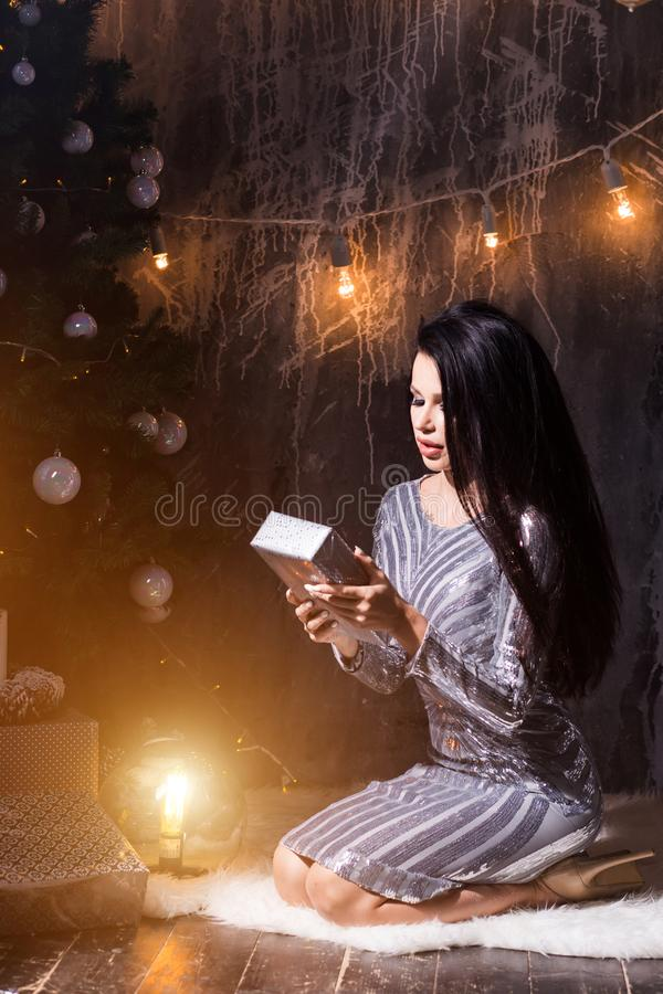 Christmas, x-mas, winter, happiness concept. New Year, holiday, celebration, winter concepts. Beautiful brunette woman in silver dress sitting near the Christmas stock image