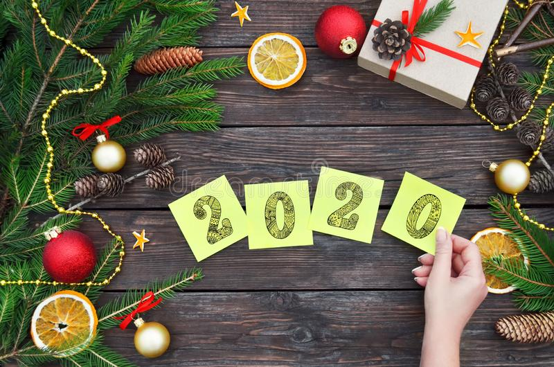 New Year holiday concept. A woman`s hand puts yellow sticky notes with the numbers 2020 on a festive wooden background stock image