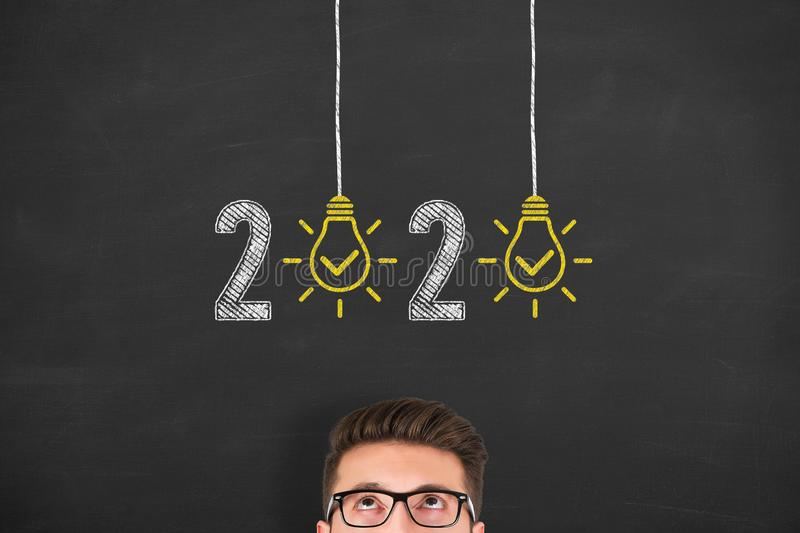New Year 2020 Idea Concepts over Human Head on Blackboard Background. New Year 2020 Idea Concepts over Human Head on Chalkboard Background new year concepts stock photo