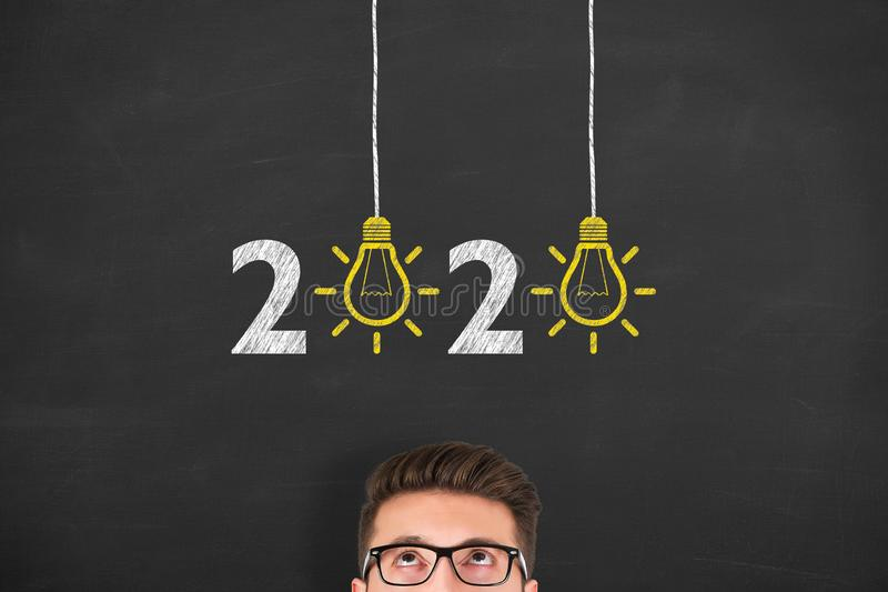 New Year 2020 Idea Concepts over Human Head on Blackboard Background. New year concepts royalty free stock photography