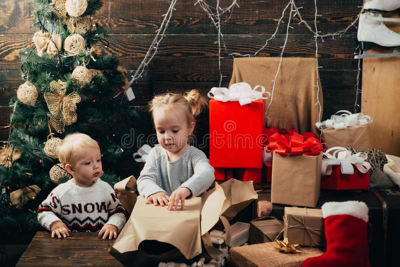 New year kids. kiddy. Child with a Christmas present on wooden background. Winter kids. Opening gifts on Christmas and stock image