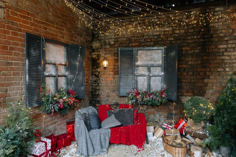 New Year and magic decorated exterior with Christmas tree, many gifts and festive lights and garlands outside of house with sofa. And plaid on background of royalty free stock photos
