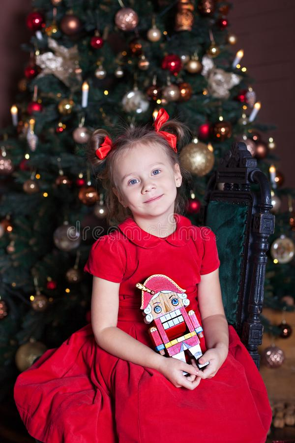 New Year 2020! Merry Christmas, happy holidays! An adorable little girl with a nutcracker in her hands sits on a chair in a beauti royalty free stock images