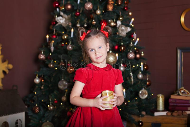 New Year 2020. Merry Christmas, happy holidays. Close-up portrait of a little girl with a candle. Little girl holds a candle in he royalty free stock photos