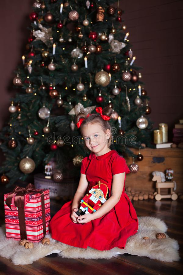 New Year 2020. Merry Christmas, happy holidays. Cute girl holds a nutcracker toy in hands in front of a Christmas tree and gifts. royalty free stock images