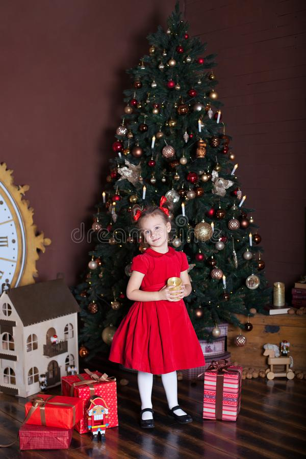 New Year 2020. Merry Christmas, happy holidays. Little girl with a candle in front of a Christmas tree and gifts. New Year decor, stock photography