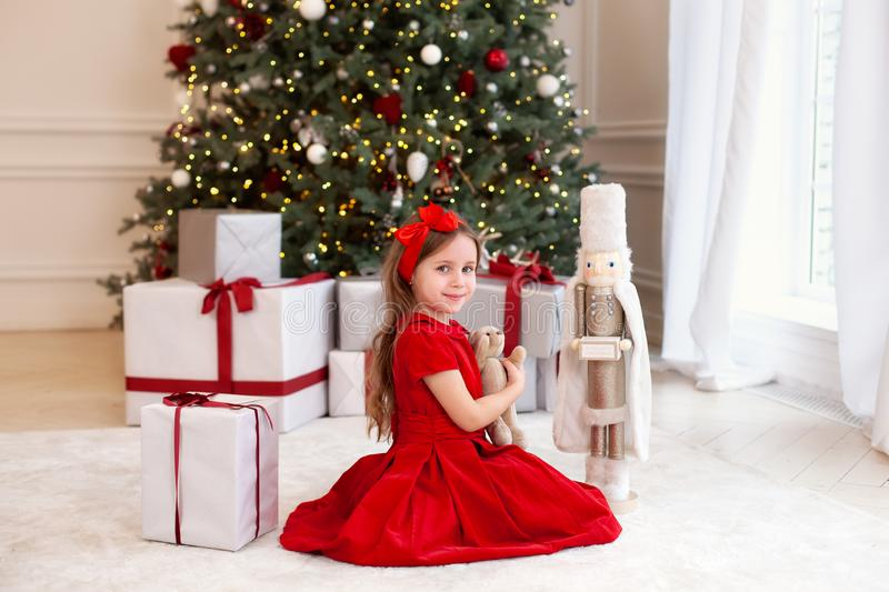 New Year 2020. Merry Christmas, happy holidays. A little girl holds a teddy bear toy in her hands in front of a Christmas tree and stock photos