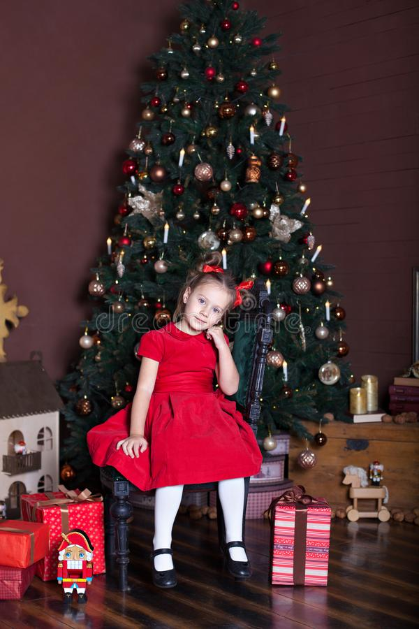 New Year 2020! Merry Christmas, happy holidays! A little girl in a red dress sits on a chair in a beautifully decorated New Year`s royalty free stock photography