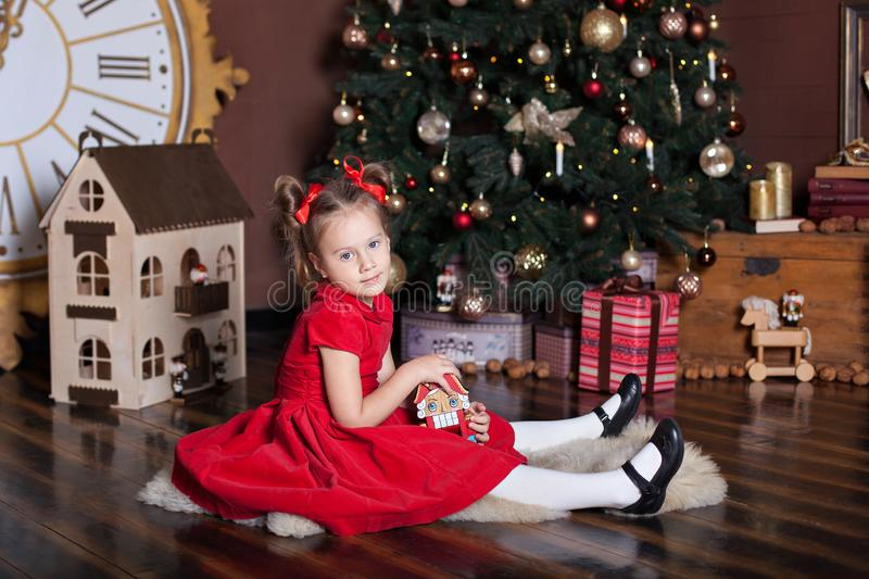 New Year 2020. Merry Christmas, happy holidays. Little girl in a red vintage dress sits near a decorated Christmas tree with a woo stock photography