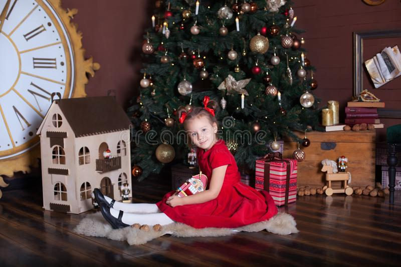 New Year 2020. Merry Christmas, happy holidays. Little girl in a red vintage dress sits near a decorated Christmas tree with a woo royalty free stock images