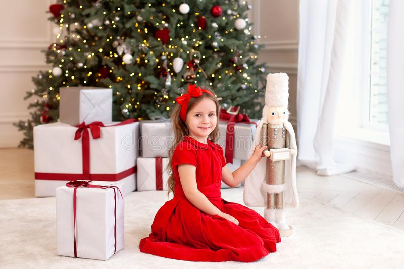 New Year 2020. Merry Christmas, happy holidays. Little girl in a red vintage dress sits near a decorated Christmas tree with a woo royalty free stock photography