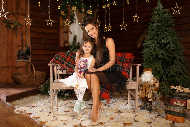 New Year 2020. Merry Christmas, happy holidays. A little girl in white dress sitting on the bench with mum. Magic Light in Night. Xmas Tree Interior stock images
