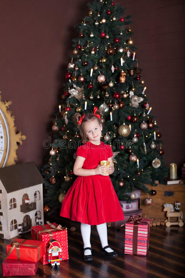 New Year 2020. Merry Christmas, happy holidays. Portrait of a little girl with a candle. Little girl holds a candle in front of a stock images