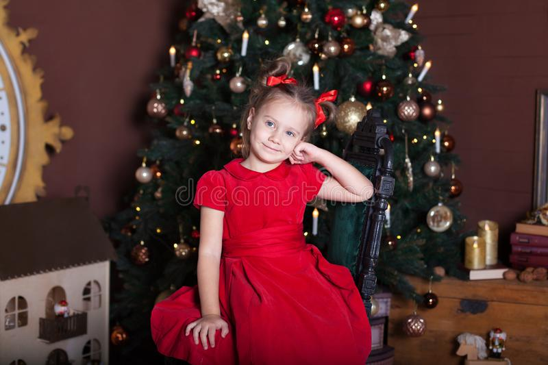 New Year 2020! Merry Christmas, happy holidays! Portrait of a little girl in a red dress and with bows on her head sits on a chair stock photos