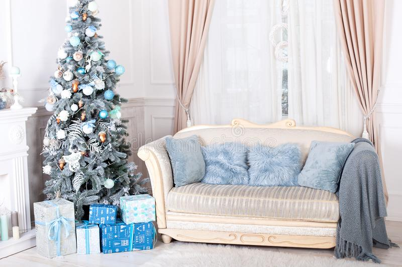 New Year 2020. Merry Christmas, happy holidays. Stylish living room interior with decorated Christmas tree, fireplace and comforta stock photography
