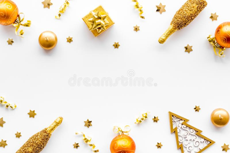 New Year mockup in gold color. Champagne bottle, present box, decoration on white background top-down frame copy space royalty free stock photography