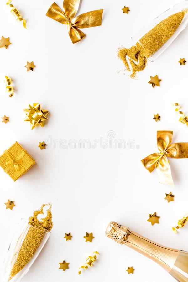New Year mockup in gold color. Champagne bottle, present box, decoration on white background top-down frame copy space royalty free stock photo