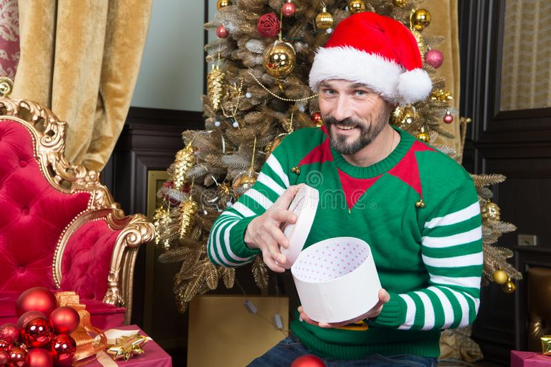 New Year mood with cheerful man opening his present and smiling. Optimistic handsome young man dressed as lovely elf smiling and looking at you while opening the royalty free stock photo