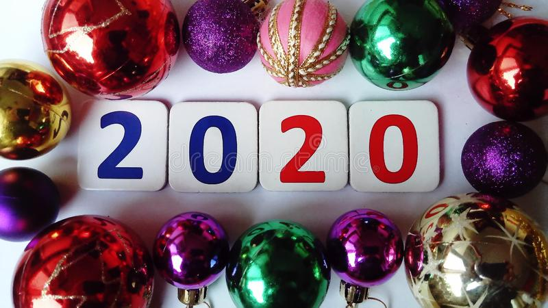 New 2020 year. The numbers 2020 are red and blue between multi-colored glass Christmas balls. Glimmers of lighting on royalty free stock images
