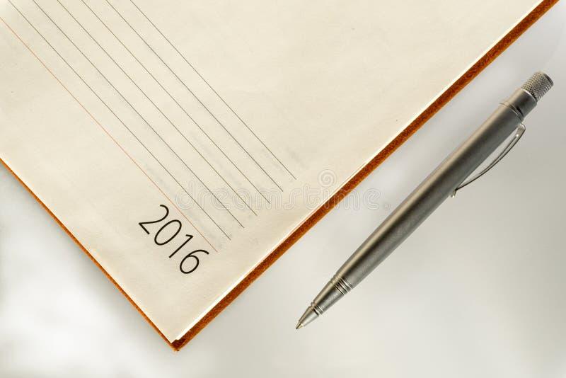 New Year 2016 office organizer calendar and sliver ballpen. Selective focus stock image