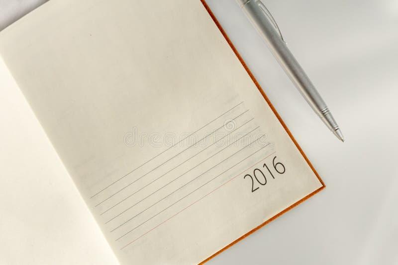 New Year 2016 office organizer calendar and sliver ballpen. Selective focus royalty free stock photos