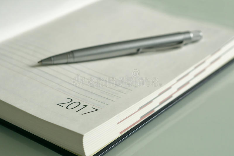 New Year 2017 office organizer. Calendar and sliver ballpen. Selective focus royalty free stock images