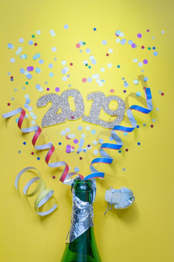 2019 new year party abstract concept with champagne and confetti on yellow background. Closeup royalty free stock images