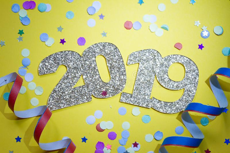 2019 new year party abstract concept with champagne and confetti on yellow background. Closeup stock photo