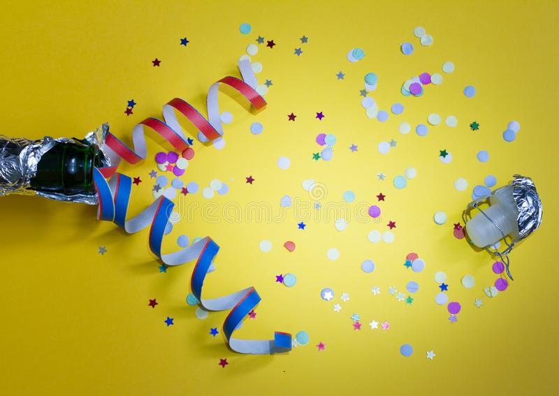 New year party abstract concept with champagne and confetti on yellow background. With empty space royalty free stock photos