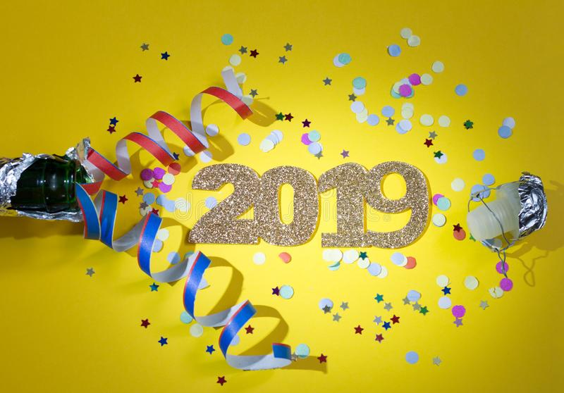 2019 new year party abstract concept with champagne and confetti on yellow background. Closeup stock image