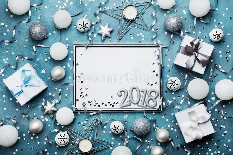New year 2018 party background. Silver frame with christmas decoration, gift box, confetti and sequins on vintage blue table. royalty free stock image