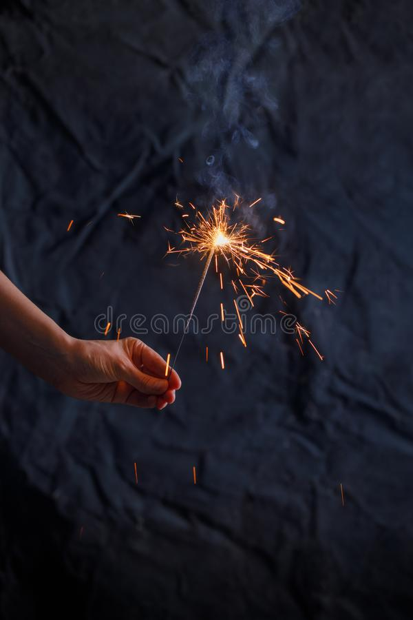 New year party burning sparkler closeup in female hand on black background. Woman holds glowing holiday sparkling hand fireworks, royalty free stock photography
