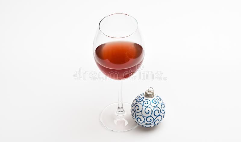 New year party concept. Wineglass with red liquid or wine and christmas ball ornament isolated on white background stock photos