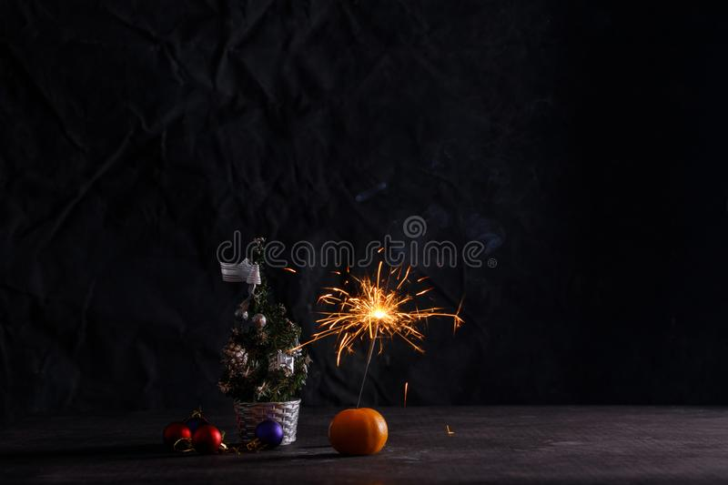 New year party sparkler on black background. Atmosphere of the New Year. Card with Christmas decorations, a mandarin and a royalty free stock images
