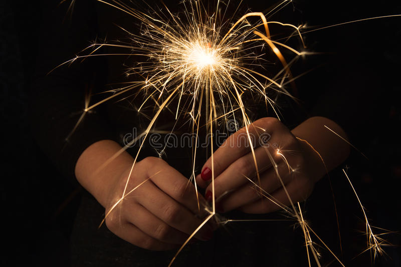 New year party sparkler in female hands on black background stock photography