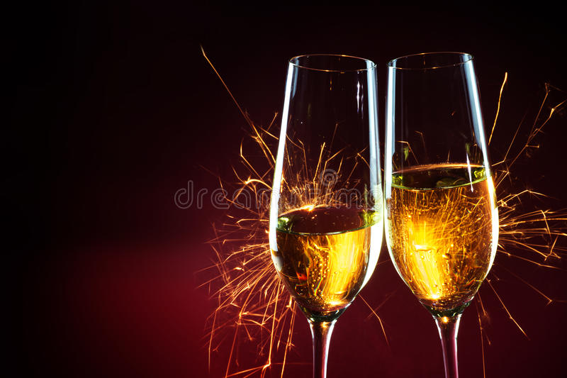 New Year party time with two champagne glasses and sparklers against a dark red background, copy space stock photography
