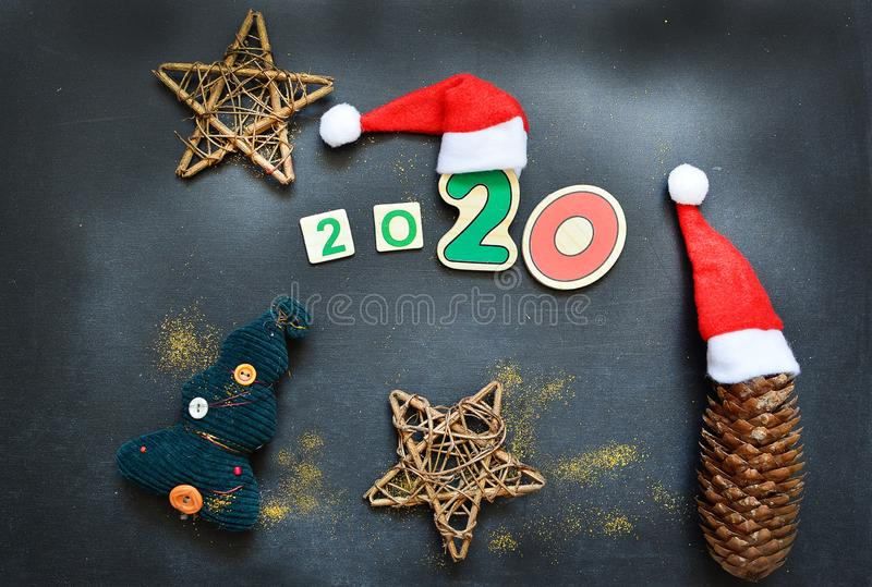New Year 2020 pattern flat lay top view with Christmas hats, Christmas tree, star on a dark background. The concept of. New Year`s holidays, Christmas stock image