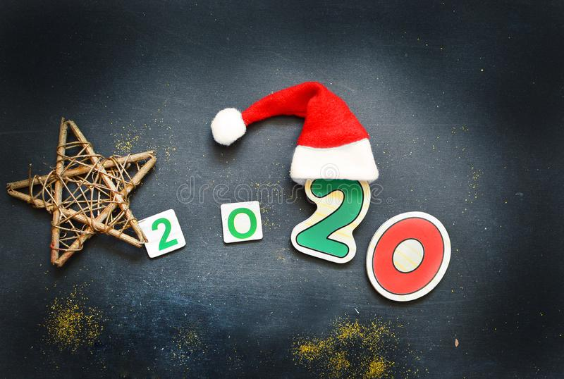 New Year 2020 pattern flat lay top view with Christmas hats, Christmas tree, star on a dark background. The concept of. New Year`s holidays, Christmas. New Year royalty free stock photography