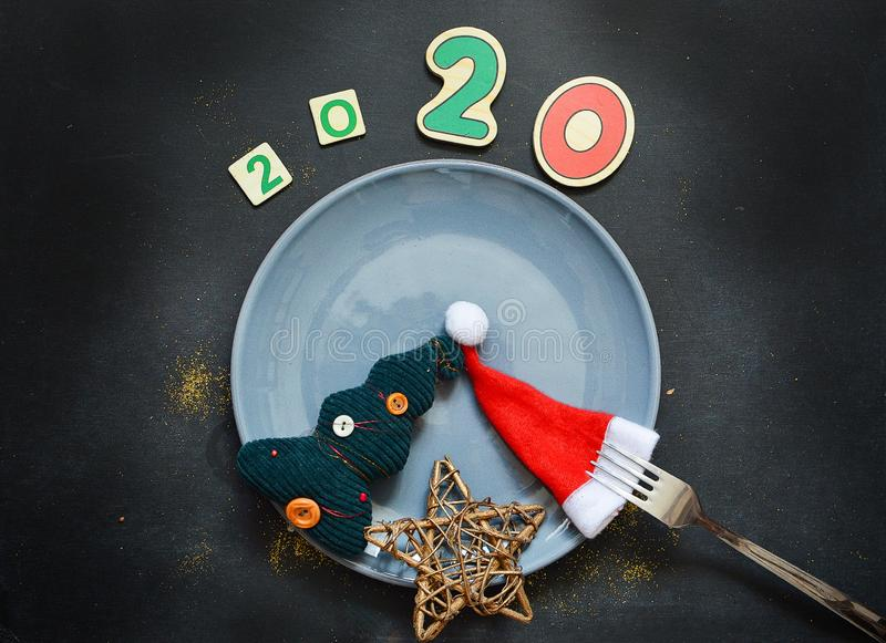 New Year 2020 pattern flat lay top view with Christmas hats, Christmas tree, star on a dark background. The concept of. New Year`s holidays, Christmas. New Year royalty free stock images