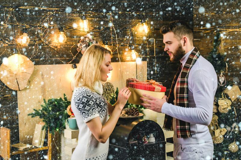 New Year photo of family. Couple in snow. New year countdown. Happy young people give each other gifts near the stock photo
