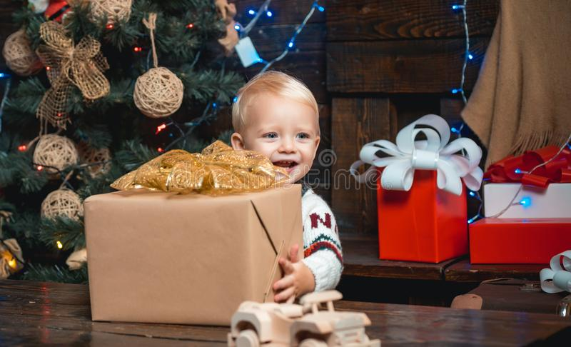 New year presents in gift box for kids. Smiling funny child in Santa hat holding Christmas gift in hand. stock photos