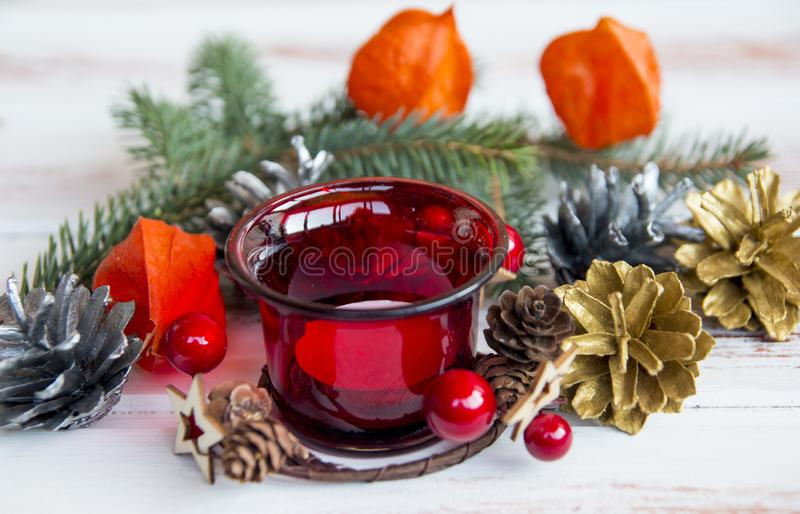 New year. Red decorated Christmas candle holder. Christmas tree decorations. Fir branches and a Golden Apple stock images