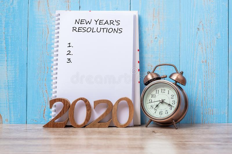 2020 New Year Resolutiions with notebook, retro alarm clock and wooden number. time for a New Start, Goals, Plan, Action and. Mission Concept stock photos