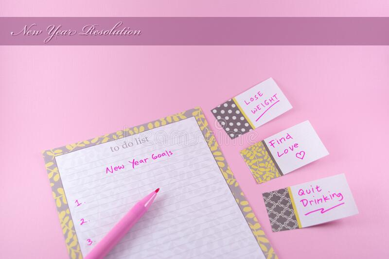 New year resolution concept and goals for greeting card template with paper and sticker on pink background. Woman or female planning royalty free stock images