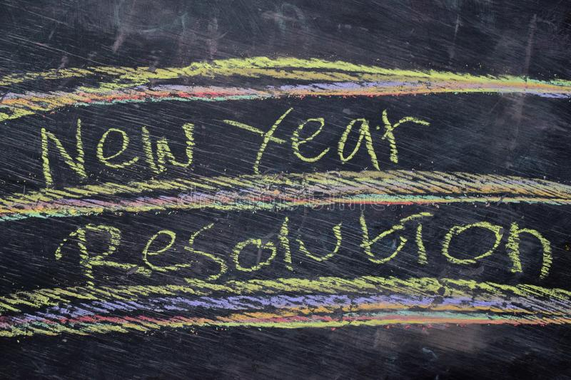 New Year Resolution handwritten text with colorful chalk on blackboard background. Inspiration, education and celebration concepts royalty free stock image