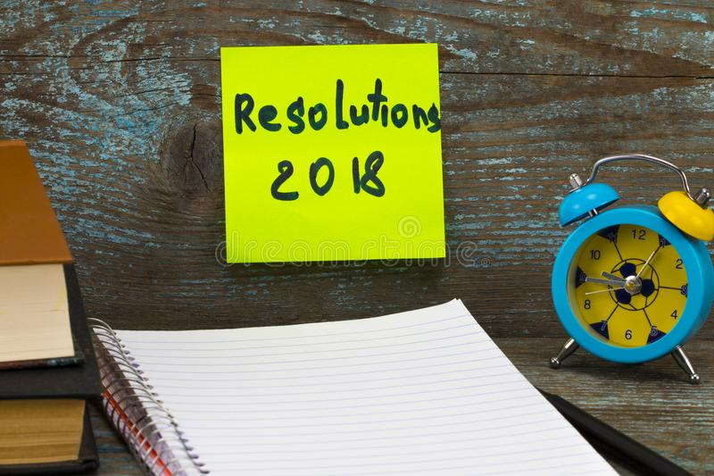2018 New year resolution on a notepad and alarm clock on wood ta stock photography