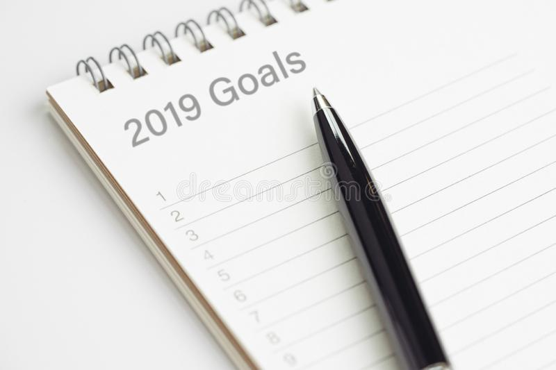 New year 2019 resolution or writing goals, to do list or work target plan concept, black pen on notepad with header as 2019 Goals. With list of numbers on white stock photo