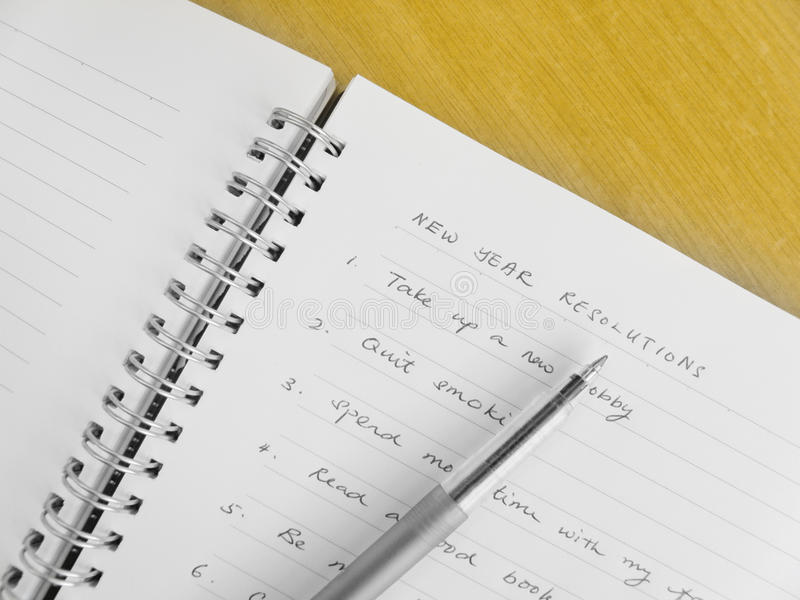New year resolutions. A photograph of a list of new year resolutions written in a ring binder note book on brown wood table. Simple composition with copy space stock images