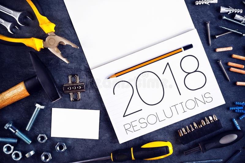 2018, New Year Resolutions Craftsman Workshop Concept. With Assorted Tools, Pencil and Notebook for Writing Goals and Aspiration in Following Year royalty free stock photography