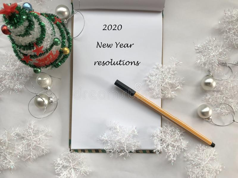 New year resolutions. 2020 new year. New year concept. White notebook sheet with pen on white background covered with christmas de.